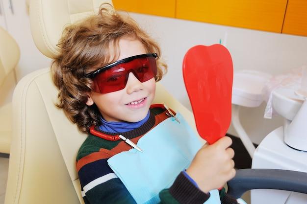Curly-haired kind verwent en grimassen in een tandartsstoel