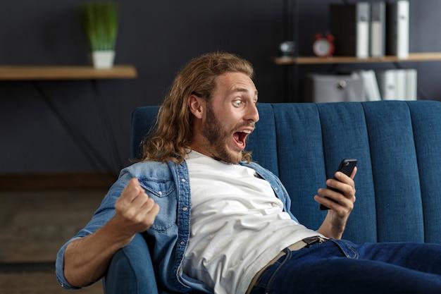 Curly-haired man in casual stijl, kijken naar geweldig nieuws op zijn mobiele telefoon. student ontvangt sms-bericht dat goed nieuws leest. verrast man viert overwinning op telefoon in appartement.