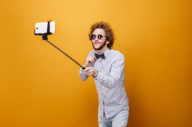 Curly-haired man in zonnebril en strikje nemen selfie met behulp van smartphone