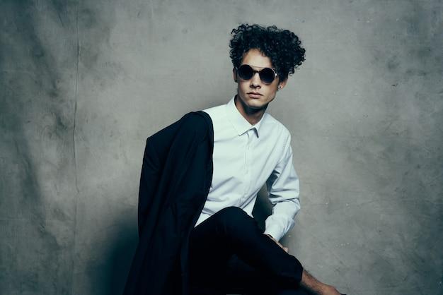 Curly haired man met bril in studio