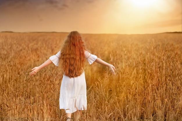 Curly-haired meisje dat van de zonsondergang op het gebied geniet.