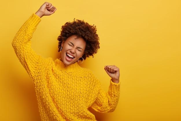 Curly haired meisje in winter gele trui dansen met armen verspreiden in de lucht, geniet van muziek, heeft dolgelukkig gezichtsuitdrukking, vormt binnen.