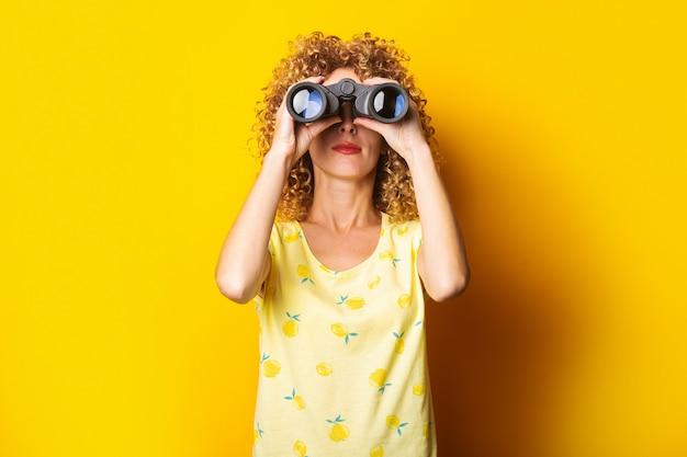 Curly-haired meisje kijkt door een verrekijker op een helder geel oppervlak