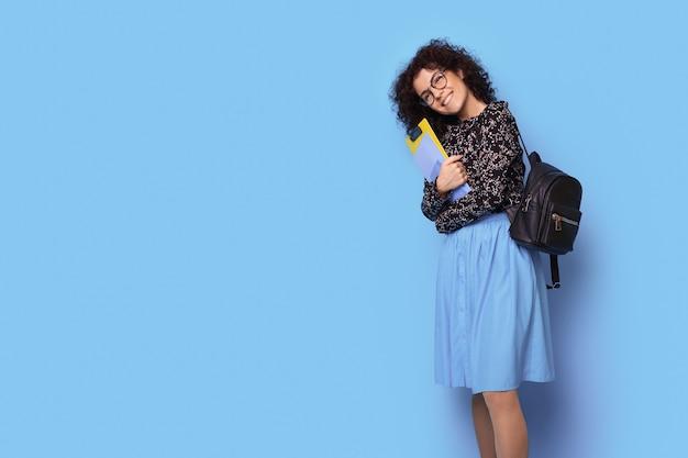 Curly haired student houdt enkele mappen en tas lachend op een blauwe studiomuur met vrije ruimte