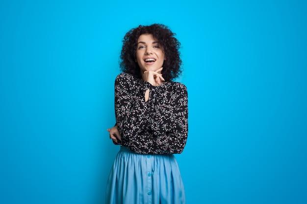 Curly haired vrouw in een blauwe jurk lacht haar kin aan te raken op de achtergrond