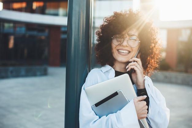 Curly haired vrouw praat over telefoon poseren buiten met een laptop bril