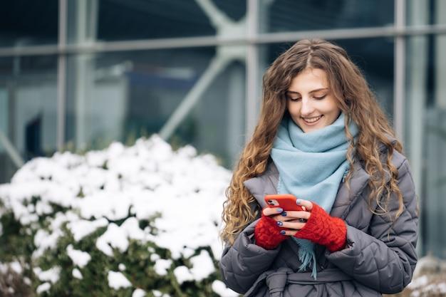 Curly-haired vrouwelijke texting op smartphone staande op straat in winter stad.