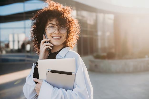 Curly haired zakenvrouw poseren buiten praten over de telefoon terwijl ze een laptop en tablet vasthoudt