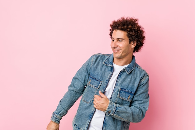 Curly volwassen man draagt een spijkerjasje tegen roze muur dansen en plezier maken.