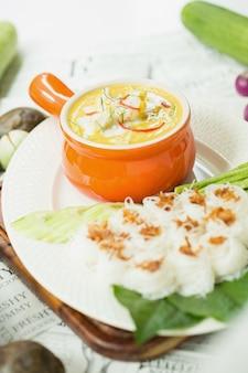 Curry crab, zeevruchten met gele kerriesaus in oranje keramische pot, op tafelkleden achtergrond