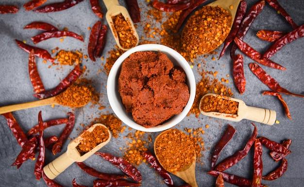 Currypasta cayennepeper op houten lepelkruiden en gedroogde chilipepers