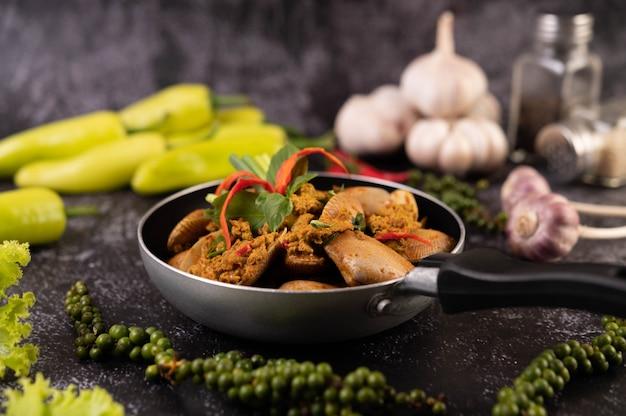 Currypoeder roergebakken op een zwarte pan met knoflook chili en basilicum.