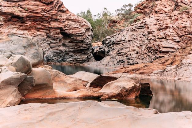 Curve en ronde rotsen in een verbazingwekkende kloof van australië. de rode ijzeren rotsen van karijini zijn een van de oudste overblijfselen van de aarde toen de zeebodem geroest werd door zuurstofvormende lagen. reizen.