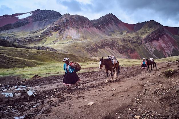 Cusco, peru. oktober 2018: peruaanse inheemse vrouw loopt en leidt een paard door de berg van de zeven kleuren. vinikunka-berg. peru