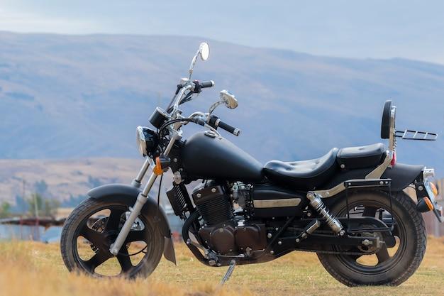 Custom-type motorfiets rustend op de route langs de weg in de andes; landschap omgeven door natuur en vegetatie als een landelijke route naar het binnenland