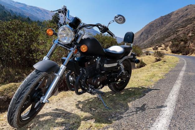 Custom-type motorfiets rustend op de route langs de weg in de andes;