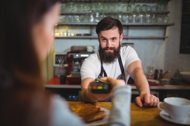Customer maken betaling via betaalautomaat bij teller