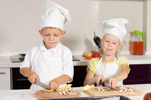 Cute kid chefs zijn bezig met het snijden van ingrediënten voor pizza in de keuken