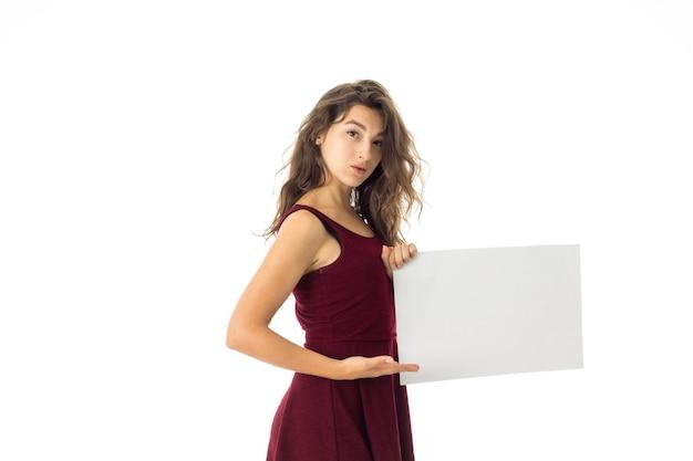 Cutie brunette jonge vrouw in rode jurk met wit aanplakbiljet in handen geïsoleerd