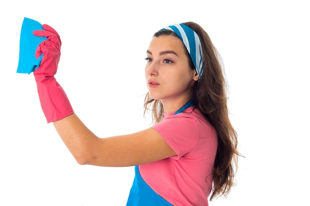Cutie jonge meid vrouw in een schort met reinigingsmiddelen geïsoleerd op een witte muur