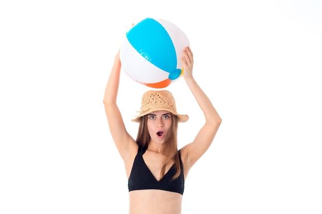 Cutievrouw in zwart zwempak met strandbal die op witte muur wordt geïsoleerd