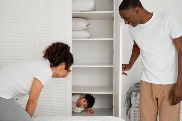 Cutle kleine jongen verstopt in de kleerkast terwijl hij verstoppertje betaalt