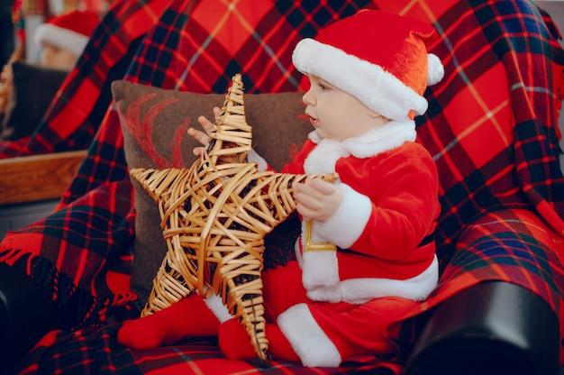 Cutte jongetje thuis in de buurt van kerstversiering