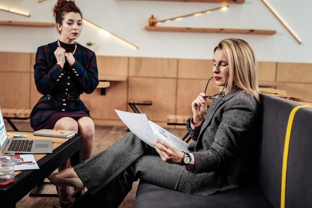 Cv studeren. blondharige welvarende zakenvrouw die cv bestudeert van haar toekomstige secretaresse