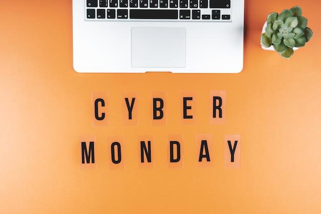 Cyber maandag op een fel oranje achtergrond met een laptop. concept van winkelen op afstand. plat liggen