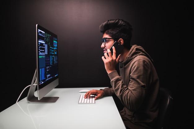 Cybercriminaliteit, hacking en technologieconcept. mannelijke hacker met smartphone en codering op computerscherm in donkere kamer