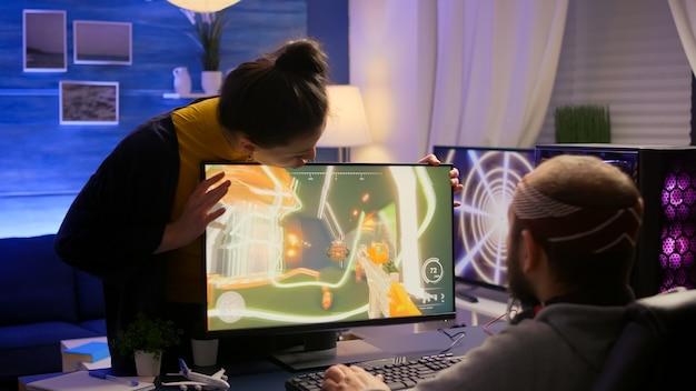Cybergamer vecht met vriendin over het spelen van first person shooter-videogame voor online competitie. pro-speler presteert op krachtige pc in de speelkamer thuis tijdens online toernooi