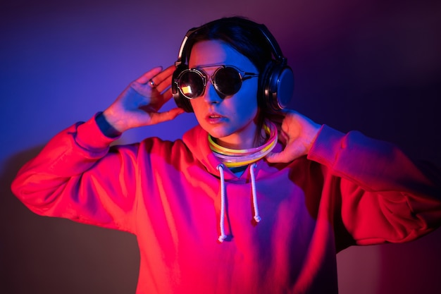 Cyberpunkvrouw in een hoodie met capuchon en zonnebril danst tegen een muur met neonstokken en koptelefoons om haar nek