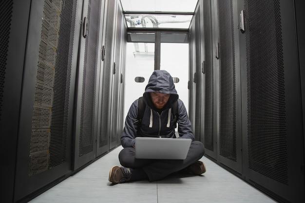 Cybersecurity. ervaren mannelijke hacker zittend op de vloer tijdens het kraken van systeem