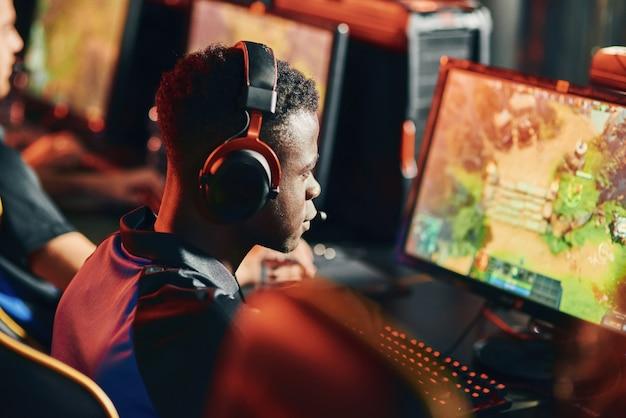 Cybersport concept achteraanzicht van een gefocuste afrikaanse man, professionele gamer met een koptelefoon op zoek