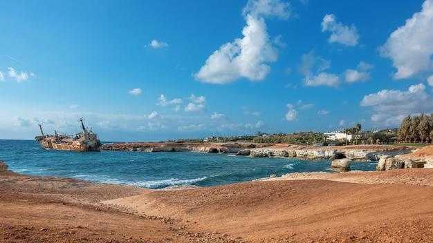 Cyprus, paphos. schipbreuk. het schip stortte neer op de kustrotsen. roestige schip aan de oever van de middellandse zee. toeristische attracties van cyprus.