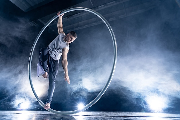 Cyr wheel circusartiest op gerookte, donkere achtergrond die op het podium optreedt