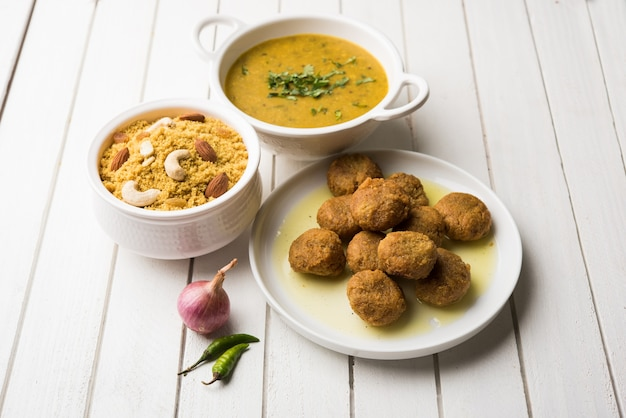 Daal baati churma is een populaire gezonde voeding uit rajasthan, india. geserveerd in wit servies op een humeurige achtergrond.