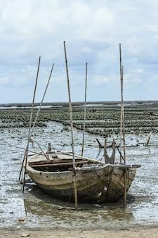 Daalde vissersboot op zandstrand en modder