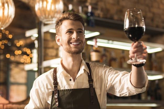 Daar ga je. vrolijke jonge barman die een glas rode wijn aan zijn klant geeft en vrolijk naar hen glimlacht