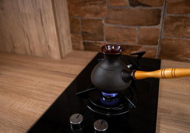 Daar staat de koffieturk op het fornuis. er brandt een vuur onder. bereiding van oosterse koffie.
