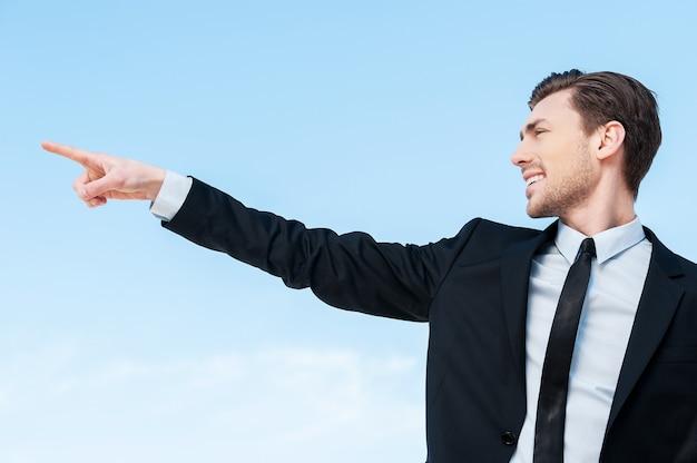 Daar... zijaanzicht van een jonge zakenman die naar de kopieerruimte wijst tegen de blauwe lucht