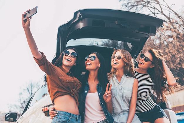 Daarom maken wij roadtrips! vier mooie jonge vrolijke vrouwen die selfie maken met een glimlach