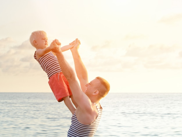 Dade houdt zijn zoon in uitgestrekte handen aan de zeekust. uitzicht vanaf de achterkant