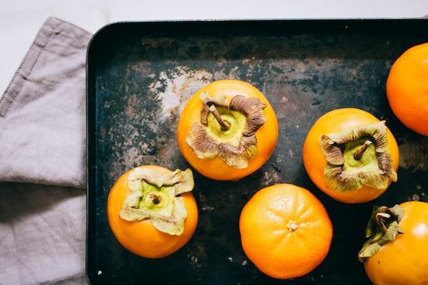 Dadelpruim en mandarijn in zwart dienblad op een marmeren achtergrond