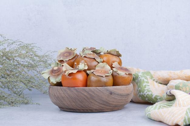 Dadelpruimen in een houten kop op grijze achtergrond