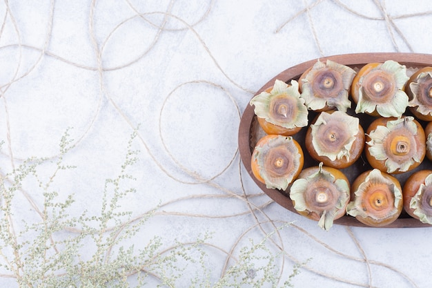 Dadelpruimen in een houten schotel op grijze achtergrond