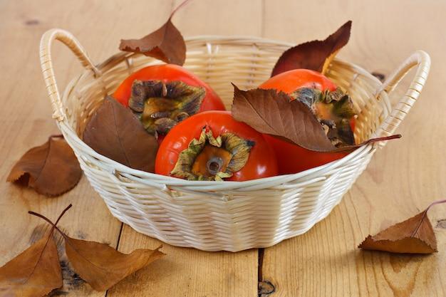 Dadelpruimen in een rieten mand op een houten bord