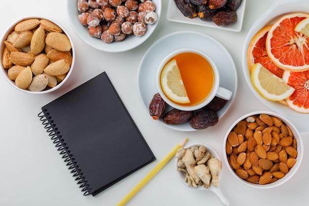 Dadels, amandelen, noten in witte borden met citroenachtige thee, gember, citrusvruchten, potlood en notitieblok plat op een witte tafel