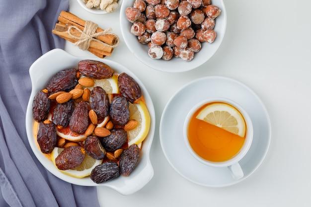 Dadels en amandelen in plaat met plakjes citrusvruchten, noten, kaneelstokjes en citroenachtige thee bovenaanzicht op textiel en witte tafel