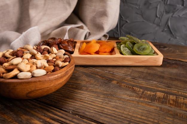 Dadels, gedroogde abrikozen en kiwi's in een compartimentenschaal en assortiment van noten in houten kom op een donkere houten tafel.